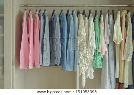 colorful women cloths hanging in wooden wardrobe