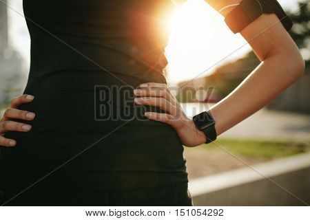 Cropped shot of fit woman in sports wear standing with her hand on hip outdoors with sun flare. Sportswoman wearing smartwatch device.