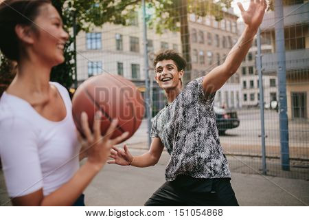 Young woman taking shot with man blocking on basketball court. Streetball players on court playing basketball.
