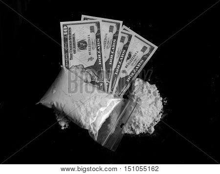 Cocaine bag, pile and dollar money bills on black background in black and white colors