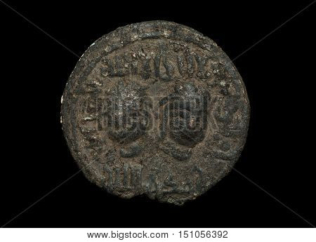 Ancient Islamic Bronze Coin With Two Faces On It Isolated On Black