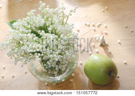 Fresh spring flowers bouquet with lily of the valley on a wooden table and green apple
