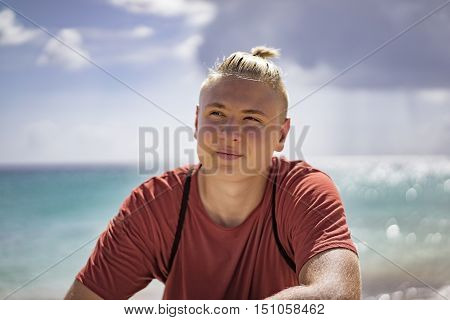 Handsome young teenage boy with his hair tied back in a small ponytail sitting at the seafront on summer vacation staring thoughtfully into the distance