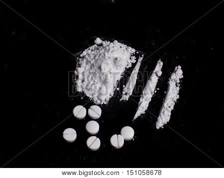 Cocaine drug powder pile, lines and pills on black background