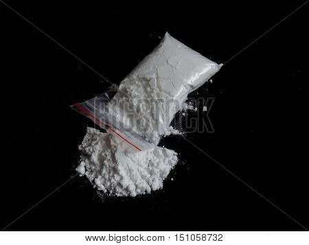 Cocaine drug powder pile and bag on black background