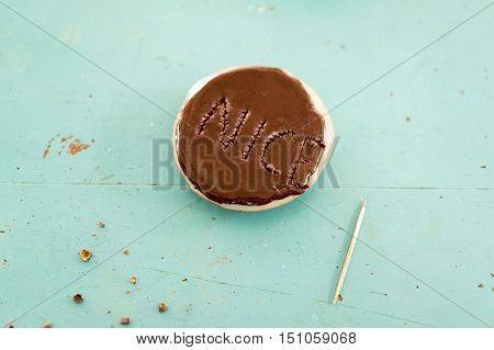 Chocolate cookie with the word Nice on it punched out with a wooden toothpick in the topping over a turquoise background with crumbs and copy space