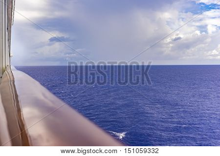 Travelling mid ocean by ferry or passenger liner with a view of a calm blue ocean looking over the rails of the ship in a concept of a summer vacation or voyage