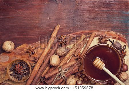 Winter spices and ingredients for cooking. Cinnamon sticks hazelnuts walnuts nutmeg cloves anise stars on an old wooden background (top view)