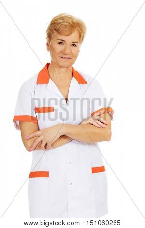 Smile elderly female doctor or nurse with folded arms