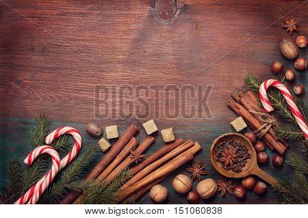 Winter spices and ingredients for cooking the Christmas meal. Cinnamon sticks hazelnuts walnuts nutmeg cloves anise stars Christmas tree branches on an old wooden background (top view)