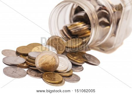 coins spilling from a money jar isolated on white
