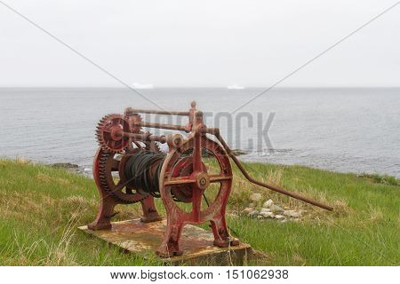 An old winch for boats with icebergs in the background.