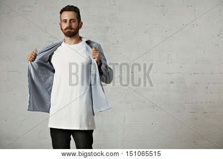 Young hipster taking off his faded blue denim button up shirt showing an unlabeled white cotton t-shirt against a brick wall background