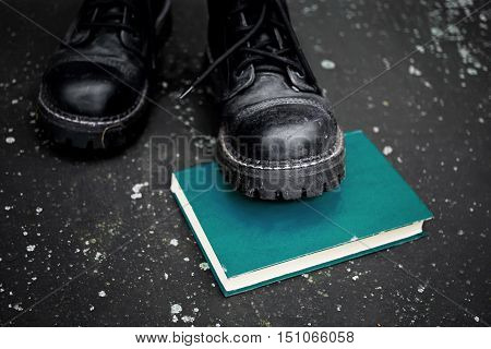 Foot wearing rough boots stepping on a book laid on the ground selective focus closeup