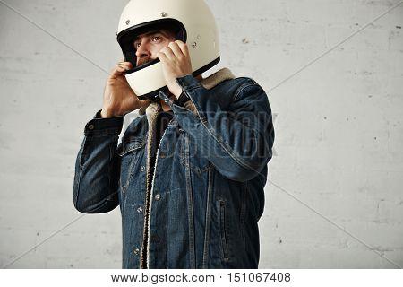 Brutal caucasian motor biker wears his helmet on head, wearing shearling denim jacket and looking on side