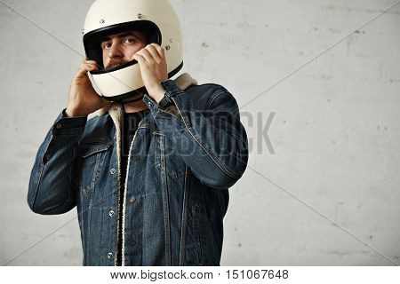 Brutal caucasian motor biker wears his helmet on head, wearing shearling denim jacket and looking on camera