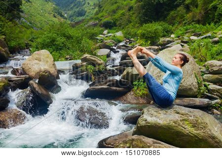 Yoga exercise outdoors -  woman doing Ashtanga Vinyasa Yoga balance asana Ubhaya padangusthasana Big Double Toe Yoga Pose at tropical waterfall in Himalayas in India