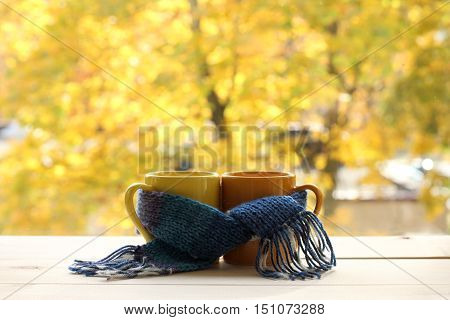 two mugs tied a warming scarf on the background of the yellowed trees outside the window / together warmer autumn