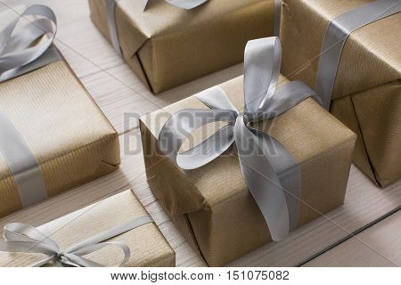 Gift boxes on white wood background. Presents in craft paper decorated with stylish elegant silver satin ribbon bows. Christmas and any other holidays concept