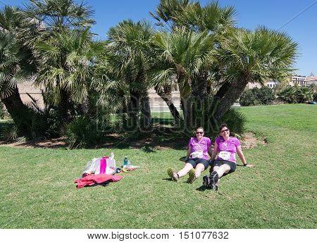 PALMA DE MALLORCA BALEARIC ISLANDS SPAIN - APRIL 10 2016: Two German ladies in purple t-shirts rest in the sun after finishing women's marathon in Palma de Mallorca Balearic islands Spain on April 10 2016.