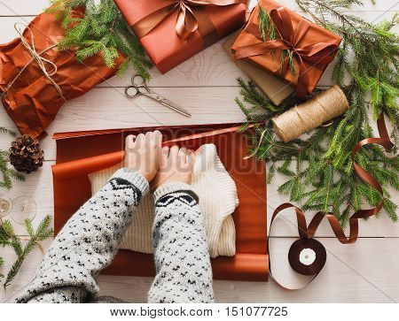 Gift wrapping background. Female hands packaging sweater as christmas present in maroon paper decorated with satin ribbon. Winter holidays concept. Top view of white wood table with fir tree branches