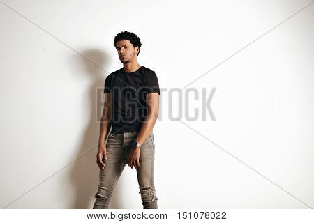 Upset tired muscular black young man in an unlabeled cotton t-shirt and skinny jeans isolated on white