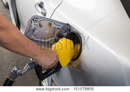 Hand With Nozzle Fueling Unleaded Gasoline Into Car