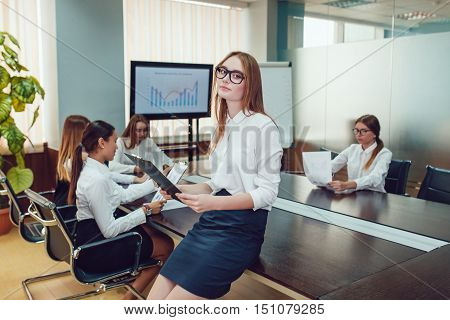 Beautiful business woman standing on the team's background with documents in hand