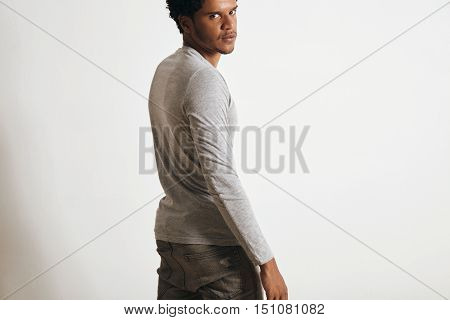 Back view of attractive latino man looking in camera turning around, isolated on white