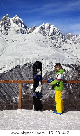 Young snowboarder with helmet in hands and snowboard on viewpoint in winter mountain at sunny day. Caucasus Mountains. Hatsvali Svaneti region of Georgia.