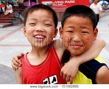 Pengzhou China - June 1 2007: Two smilug Chinese best friends walking iu New Square