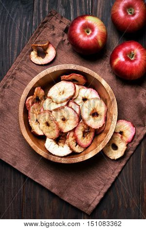 Baked dehydrated apples chips in wooden bowl healthy snack