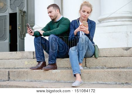 A 30s couple chatting with their smart-phone