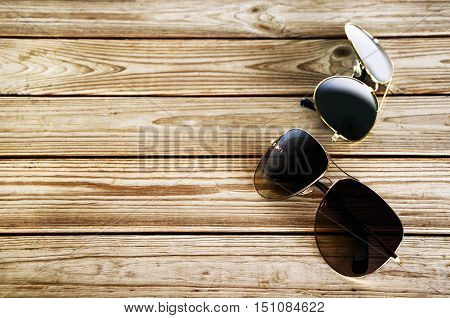 Two Unisex Sunglasses On A Wooden Background Top View