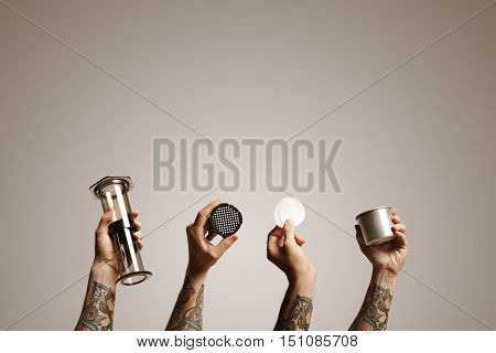 Empty clear aeropress, filter cap, two paper filters and steel travel cup held up in the air by four hands against white background Alternative coffee brewing commercial