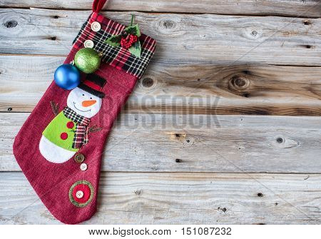 horizontal image of a great idea for christmas card with a red weave stocking with a plaid cuff and a snowman on it adorned with two christmas balls on an old wood knotty background.