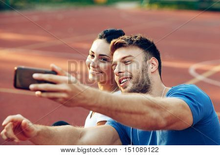 Selfie of young happy couple on the basketball court