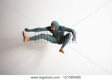 Happy smiling bearded young athlete wearing thermal baselayer suite and jumping like a ninja in air, kicking his leg on side, isolated on white