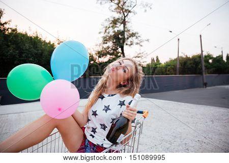 Portrait of happy smiling blonde woman having fun alone in shopping trolley