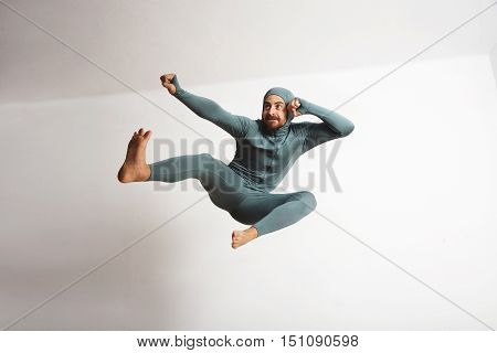 Young and fitted bearded athlete male wearing his winter snowboardint baselayer thermal suite and having fun acting like a ninja, jumping with leg kicks in air