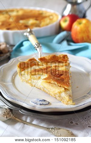 Apple tart with cream and two red apples