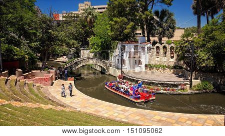 SAN ANTONIO, TEXAS - APRIL 14: Tourists visit the Arneson River Theatre and famous River Walk in downtown San Antonio, Texas on April 14th, 2016.