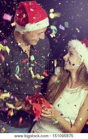 Couple in love having fun at New Year's party wearing Christmas hats and exchanging presents