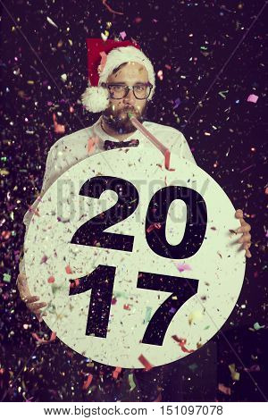 Handsome young hipster guy having fun at New Year's party wearing Santa's hat blowing party whistle and holding a cardboard circle with 2017 written on it