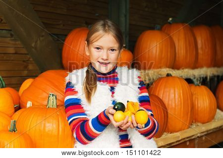 Adorable little girl of 8-9 year old choosing halloween pumpkin on farm market