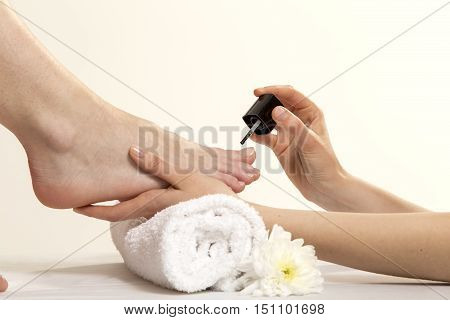 Closeup View Of A Beautician's Hand Applying Nail Varnish To Woman's Feet