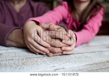 Close up. Unrecognizable granddaughter holding hands of her grandmother. Studio shot on white wooden background.