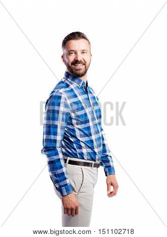 Young handsome hipster man in checked blue shirt, arms crossed. Studio shot on white background, isolated.