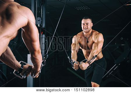 Bodybuider demonstrate crossover exercises in the gym