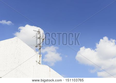 The analog TV antenna on the building with the cloud sky